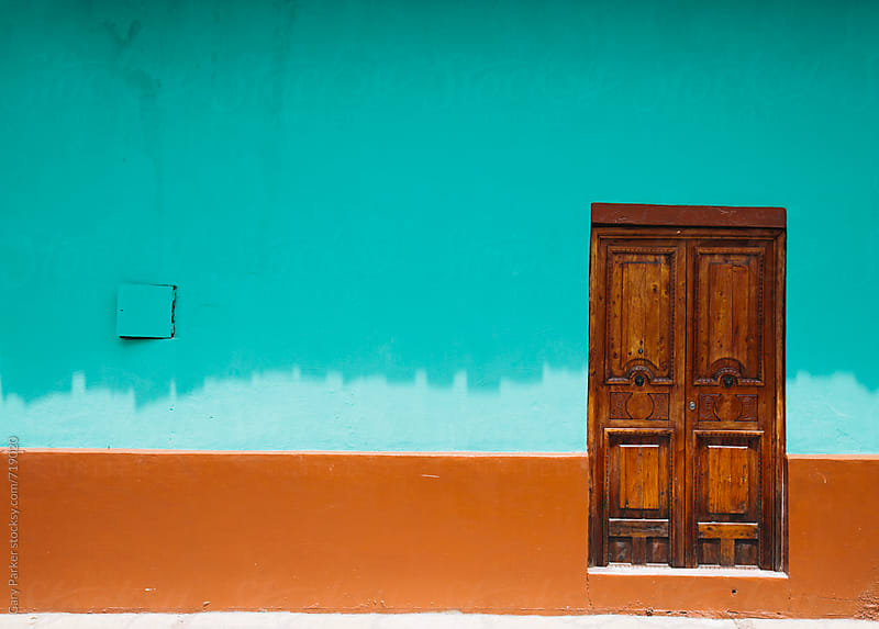 Wooden door with bright orange and aqua painted wall by Gary Parker for Stocksy United