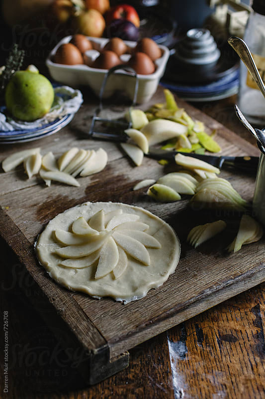 Making pear galettes: messy table setting mid prep for sweet/savory dessert dish. by Darren Muir for Stocksy United