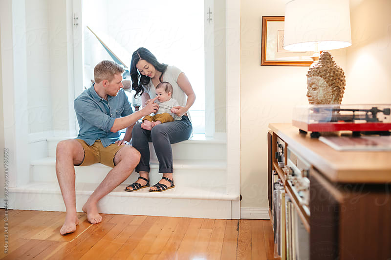 Young family enjoying each other inside by Rob and Julia Campbell for Stocksy United