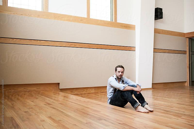 Man wearing suspenders sitting in an open studio by J Danielle Wehunt for Stocksy United