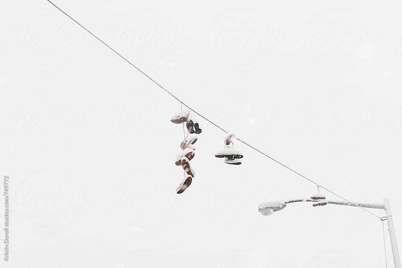Sneakers hanging from line during snowstorm. Brooklyn. by Kristin Duvall for Stocksy United