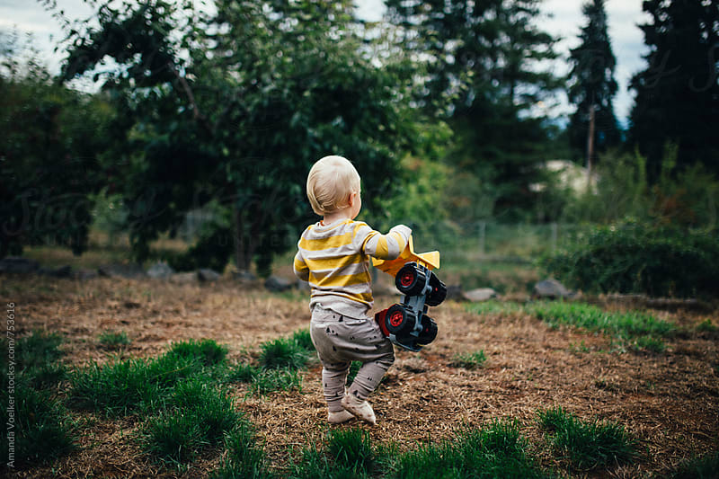 A Toddler Boy Walks Across the Yard Carrying his Toy Truck by Amanda Voelker for Stocksy United