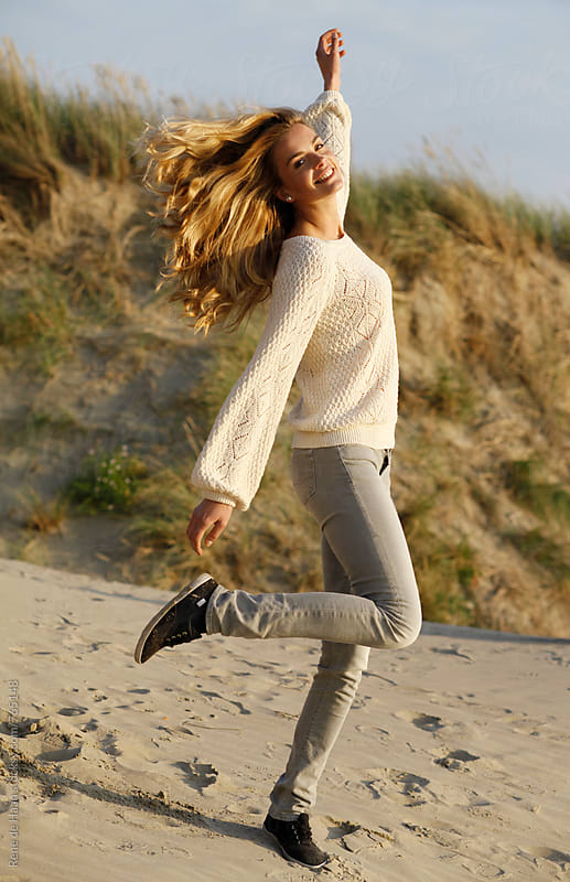 happy young woman on beach  by Rene de Haan for Stocksy United