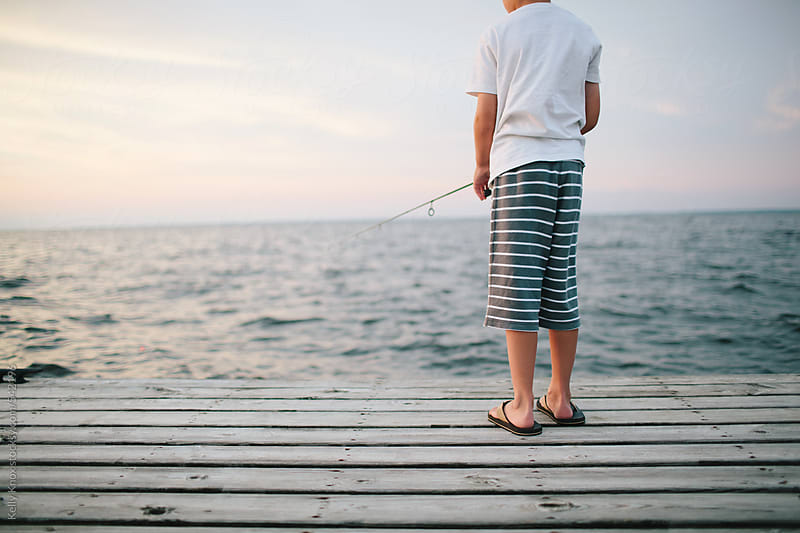 boy fishing on a pier at sunset by Kelly Knox for Stocksy United