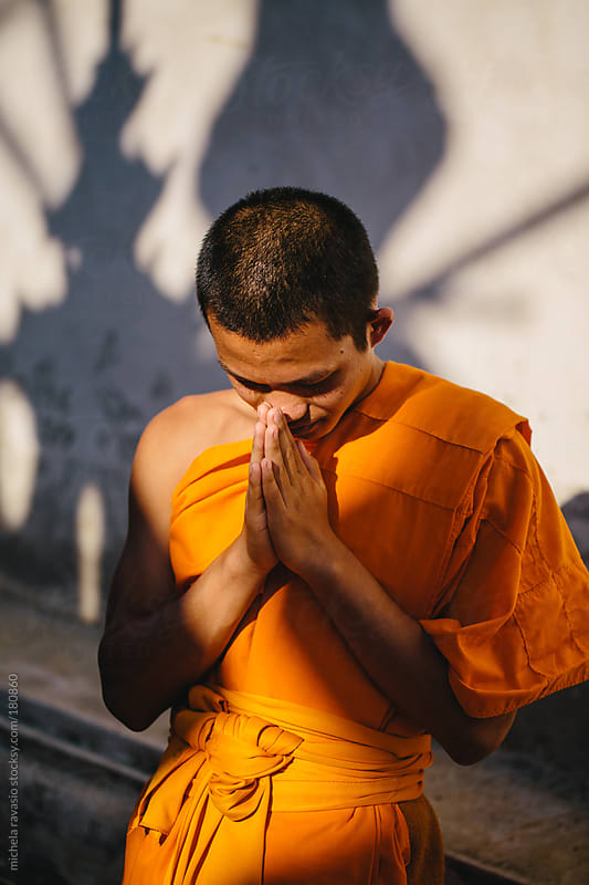 Portrait of a young Buddhist monk praying by michela ravasio for Stocksy United