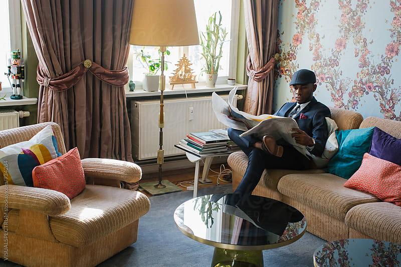 Stylish Elegant Young Black Man Reading Newspaper in Beautiful Living Room by VISUALSPECTRUM for Stocksy United