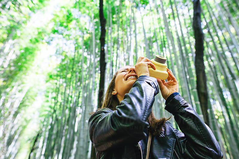 Woman taking a photo of bamboo forest. by BONNINSTUDIO for Stocksy United