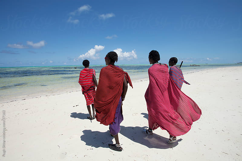 Maasai tribesmen walking along beach in Zanzibar. Tanzania. by Hugh Sitton for Stocksy United