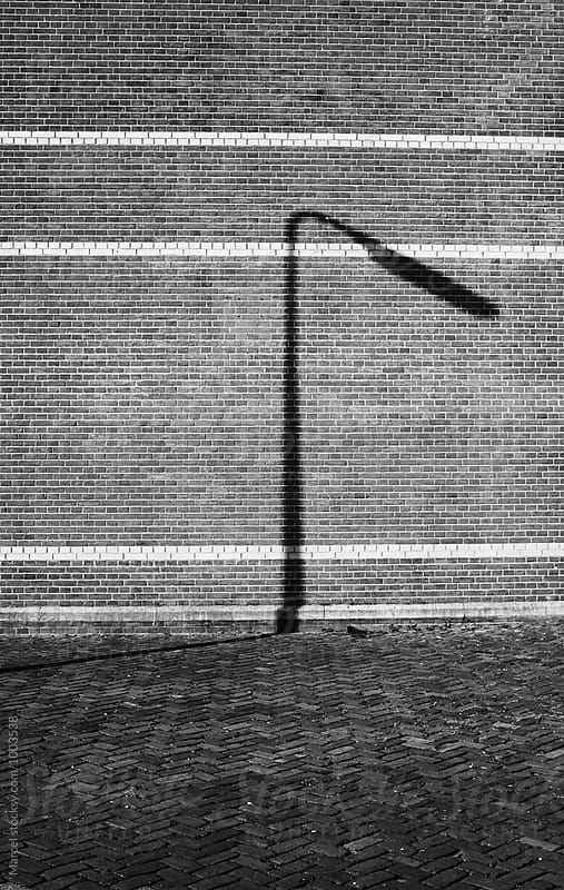 Shadow of a lamppost by Marcel for Stocksy United