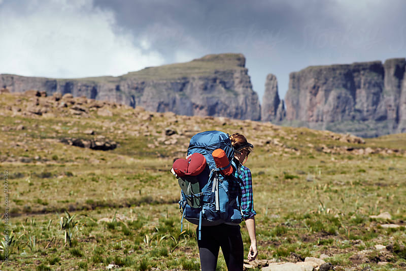 Female hiker with her back pack hiking through a field surrounded by mountains. by Jacques van Zyl for Stocksy United