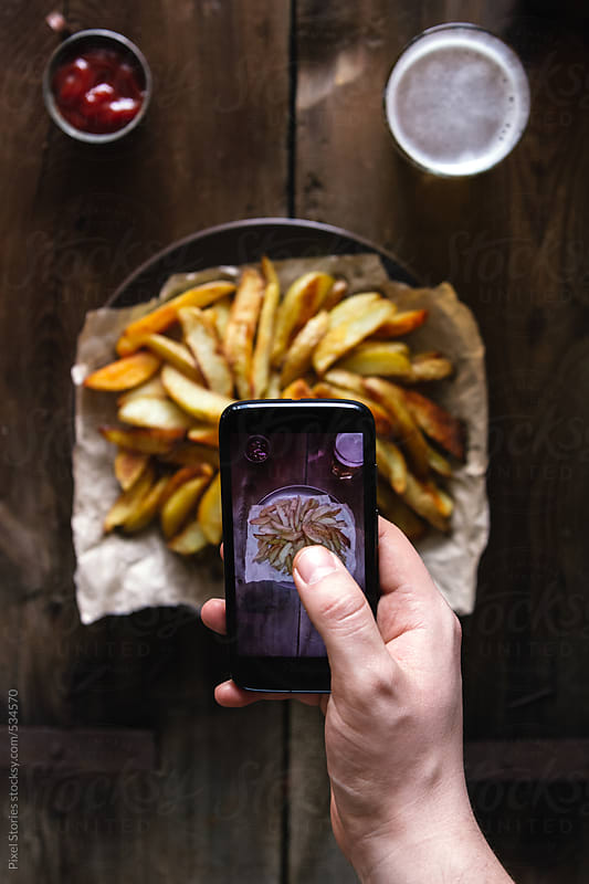 Food: person taking mobile photo of potatoes dish by Pixel Stories for Stocksy United