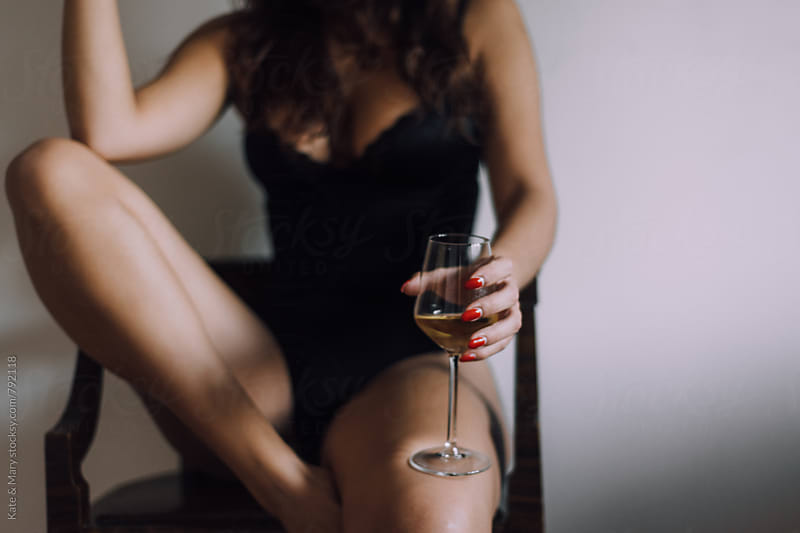 Sensual woman holding a glass of wine by Katarina Simovic for Stocksy United