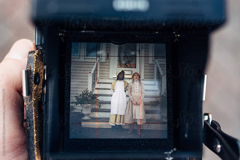 African American and Caucasian girls in old-fashioned dresses in a camera viewfinder by Gabriel (Gabi) Bucataru for Stocksy United