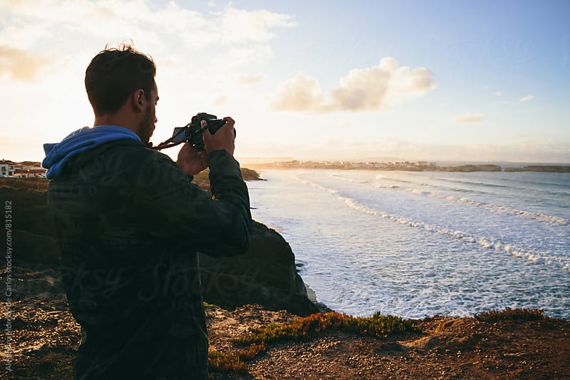 Young man looking at his camera taking pictures from the edge of the shore of the sea during sunset by Alejandro Moreno de Carlos for Stocksy United