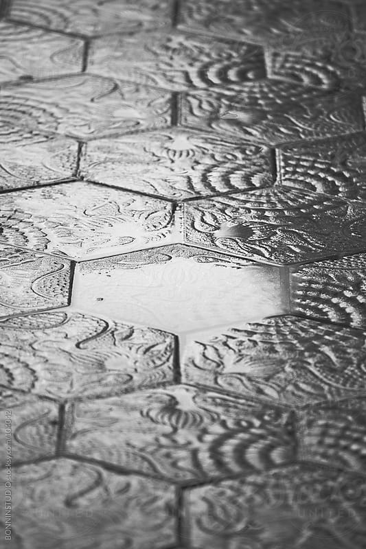 Modernist tiles of Barcelona streets on rainy day.  by BONNINSTUDIO for Stocksy United