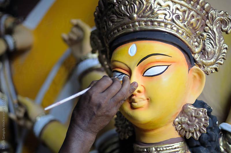Artist painting the eye of idol of Hindu goddess Durga by Saptak Ganguly for Stocksy United