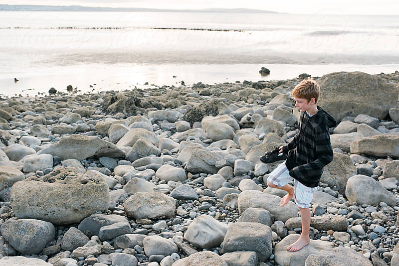 teen walking on rocky beach by Léa Jones for Stocksy United