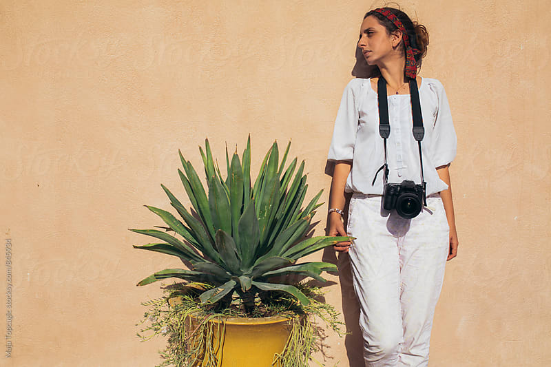 Female photographer standing next to aloe vera plant by Maja Topcagic for Stocksy United