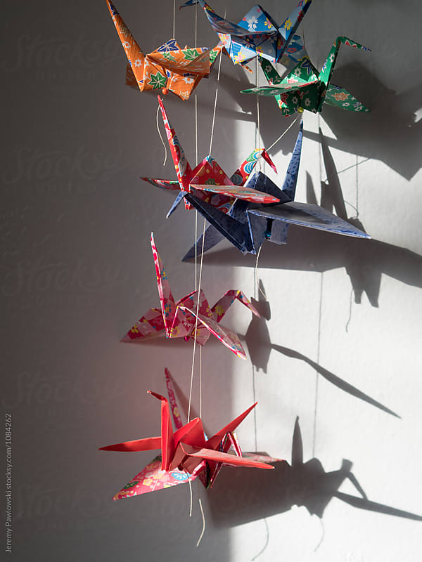 Japanese origami cranes hanging in bedroom by Jeremy Pawlowski for Stocksy United