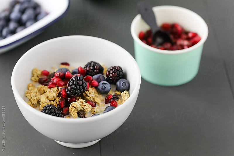 Granola in bowl with berries and pomegranate seeds by Kirsty Begg for Stocksy United