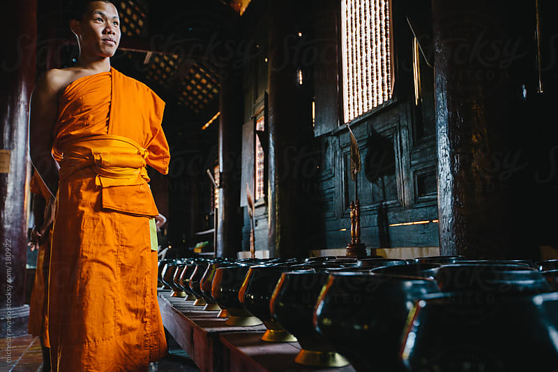 Young Buddhist monks walking in the temple by michela ravasio for Stocksy United