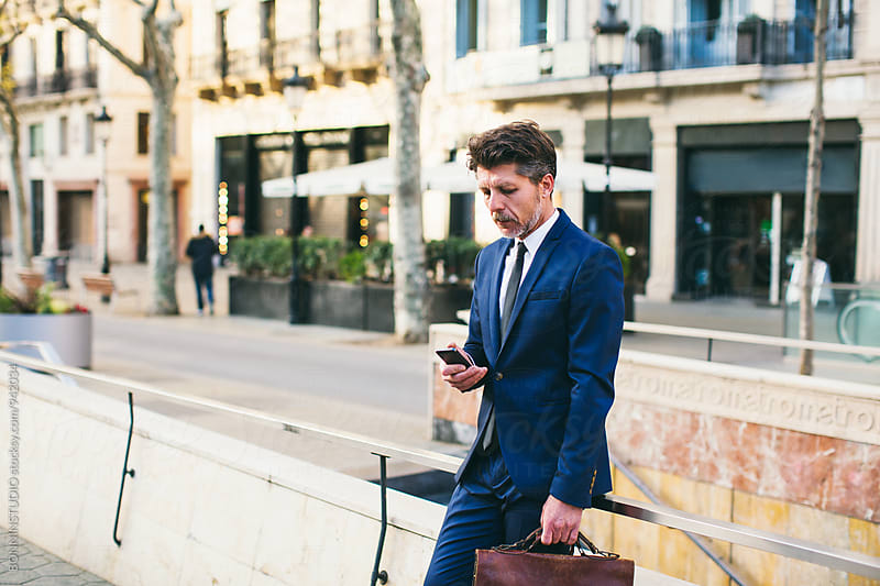 Mature businessman using his phone on the street. by BONNINSTUDIO for Stocksy United