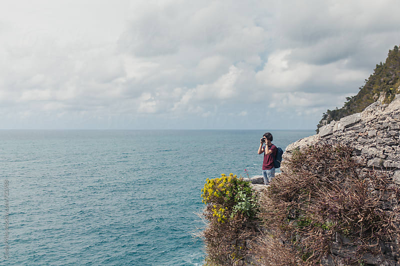 Teenage boy standing on a rock photographing the ocean by Cindy Prins for Stocksy United