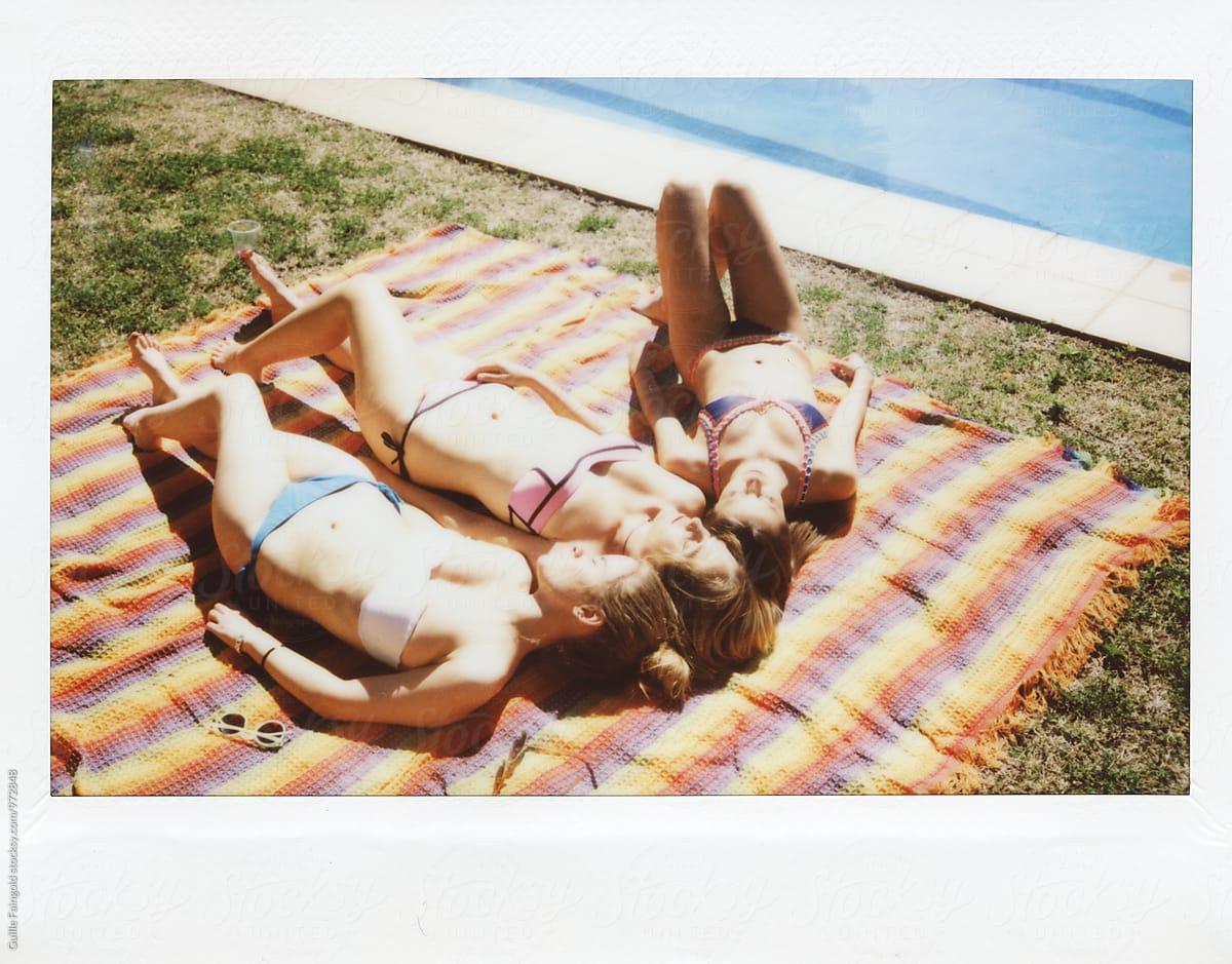 Three girls getting tanned on backyard near swimming pool ...