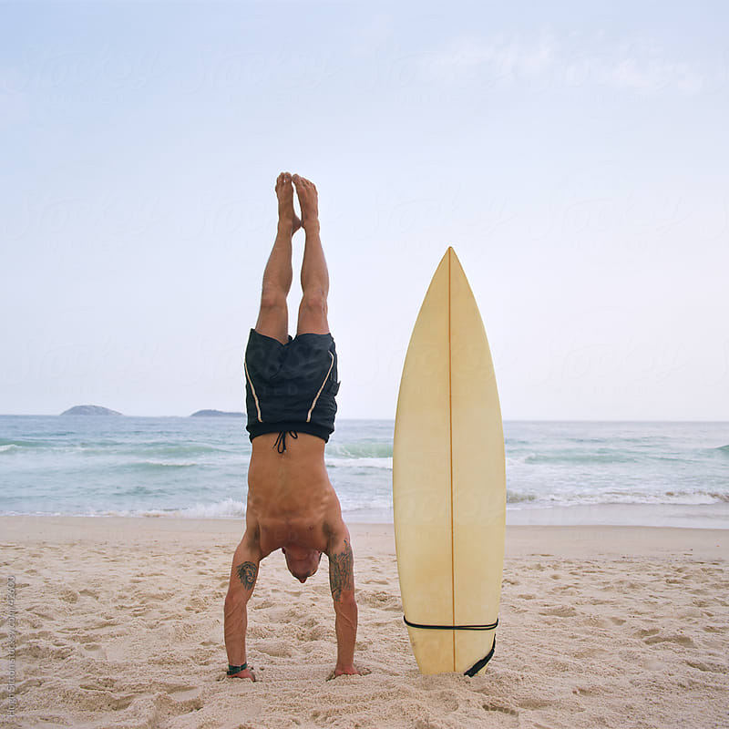 Surfer on beach with board by Hugh Sitton for Stocksy United