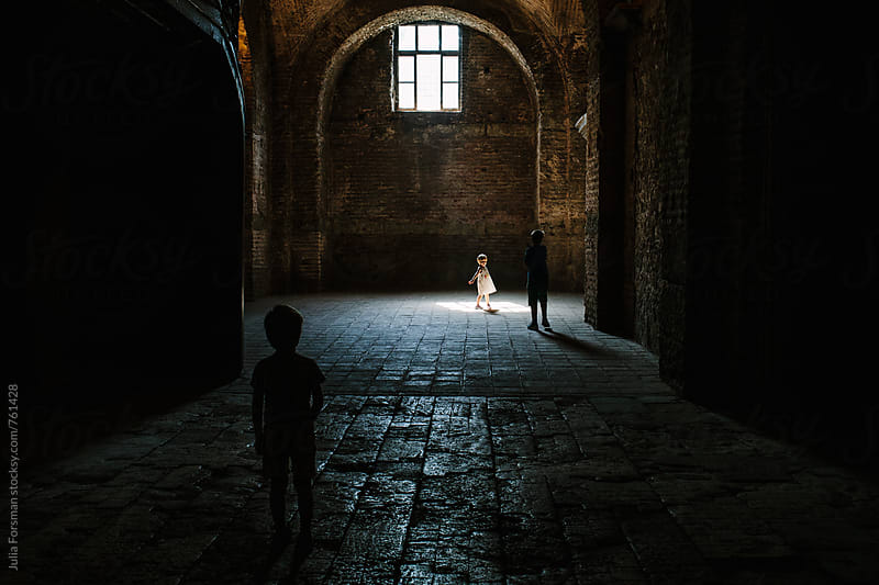 Little girl runs into light on the floor of a historical building from a window high above her.  by Julia Forsman for Stocksy United