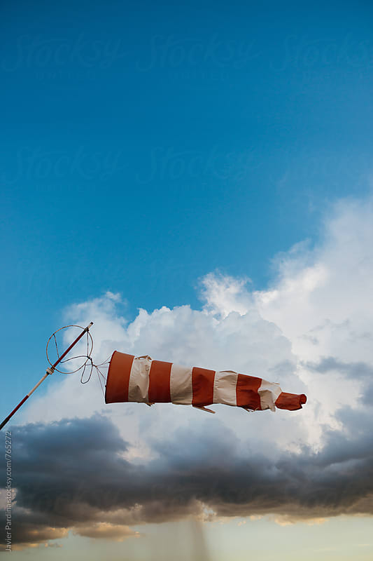 old windsock in a stormy sky by Javier Pardina for Stocksy United