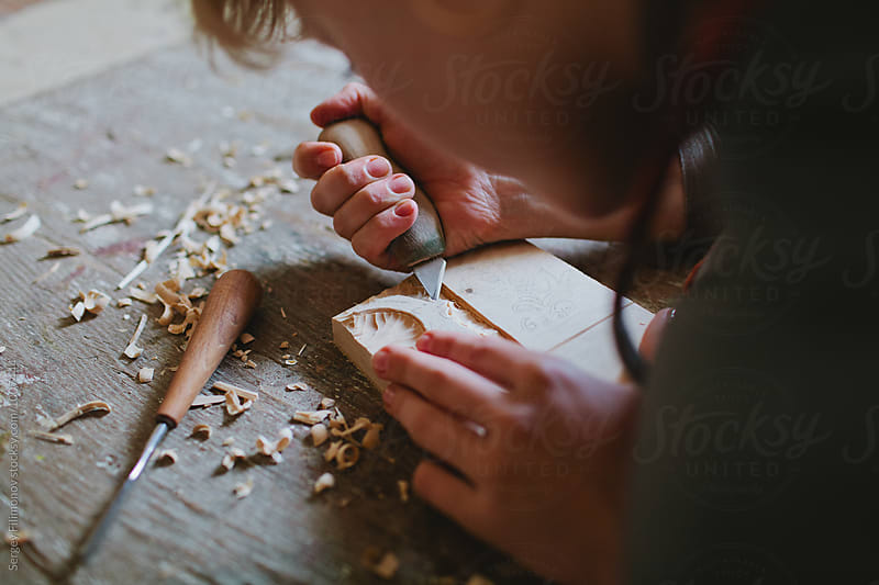Girl is engaged in wood carving by Sergey Filimonov for Stocksy United