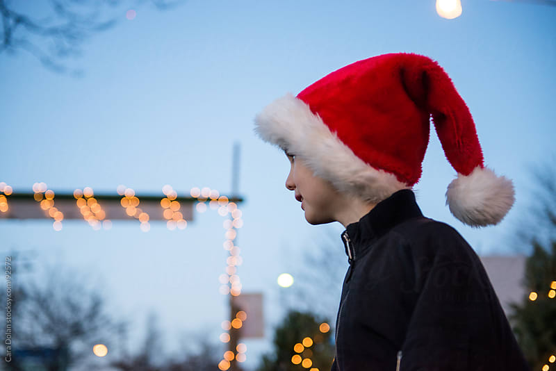 Happy boy wearing Santa hat at Christmas tree stand by Cara Dolan for Stocksy United