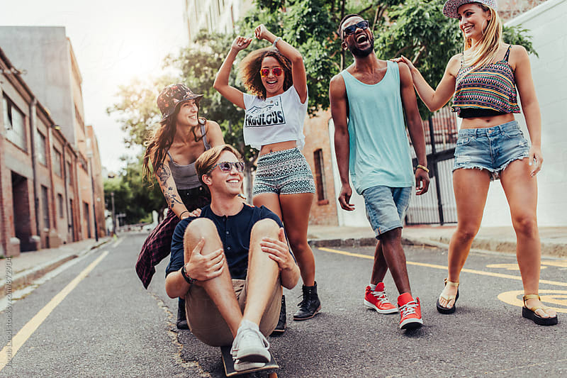 Happy group of young people walking on city street by Jacob Ammentorp Lund for Stocksy United
