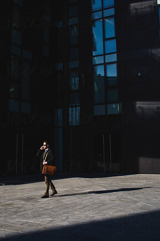 Young man walking outdoor office building holding his cell by michela ravasio for Stocksy United