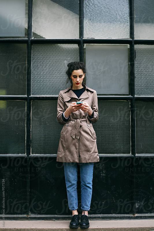 Stylish woman using her mobile phone by Marija Kovac for Stocksy United