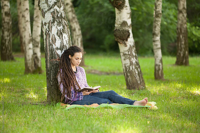 Woman reading a book in a park. by Mosuno for Stocksy United
