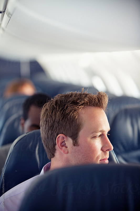 Airplane: Man Gazes Out Window by Sean Locke for Stocksy United