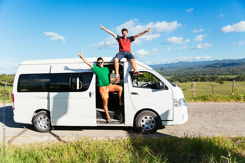 Two excited young men saluting from their white minivan during a break stopover in the middle of the road in the countryside by Alejandro Moreno de Carlos for Stocksy United