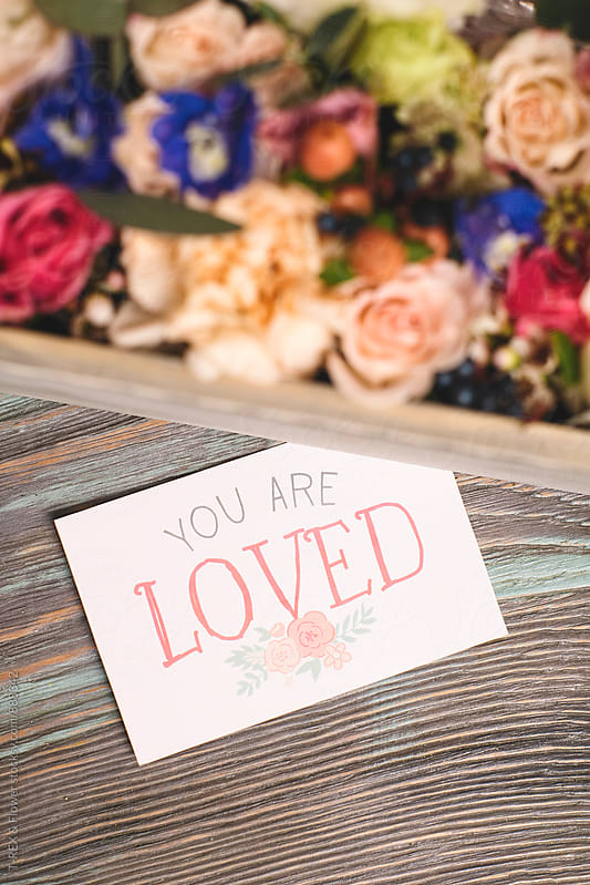 Close-up of card 'you are loved' near box of flowers by Danil Nevsky for Stocksy United
