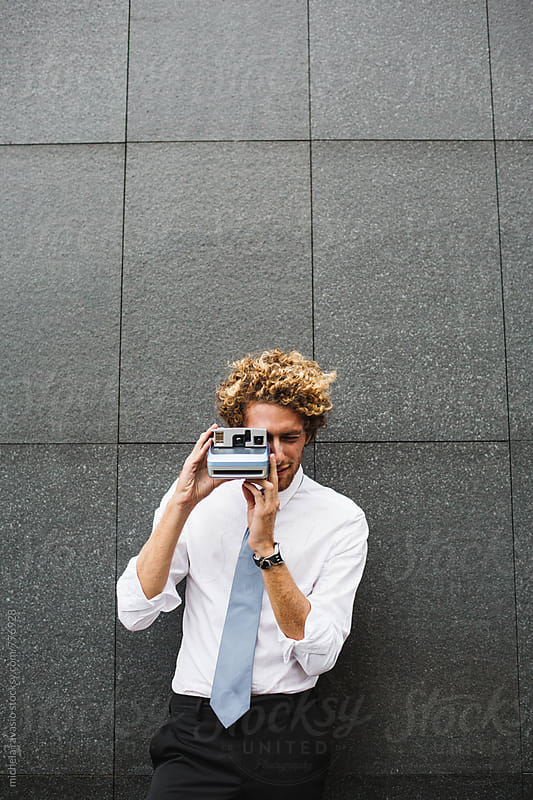 Young man taking pictures with a vintage camera by michela ravasio for Stocksy United