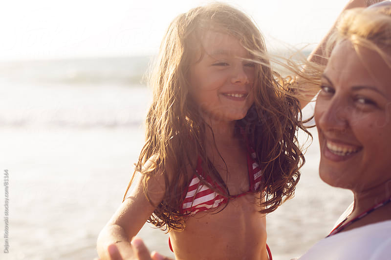 Mother having fun with her daughter on the beach by Dejan Ristovski for Stocksy United