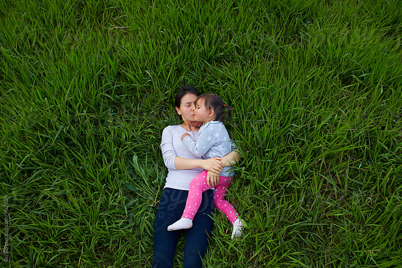 mother holding her little girl lying in the grass by cuiyan Liu for Stocksy United