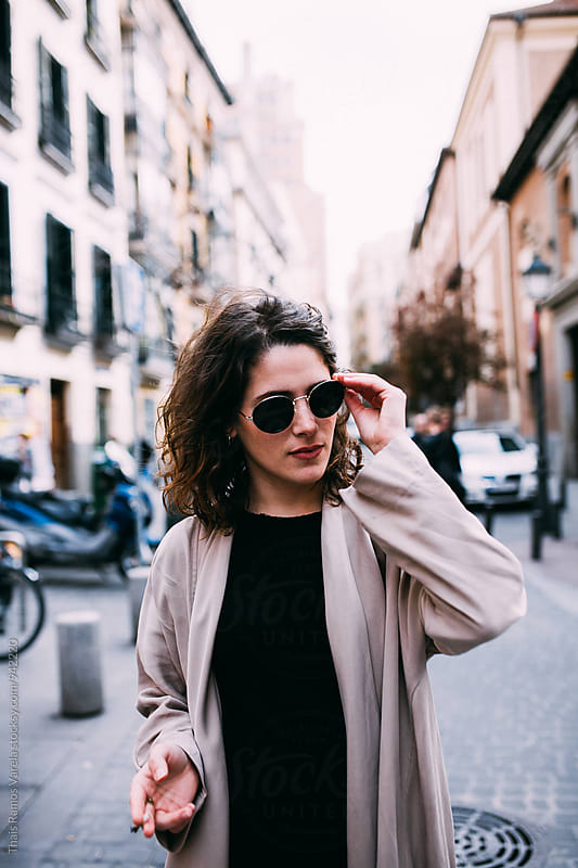 woman wearing sunglasses in the strret by Thais Ramos Varela for Stocksy United
