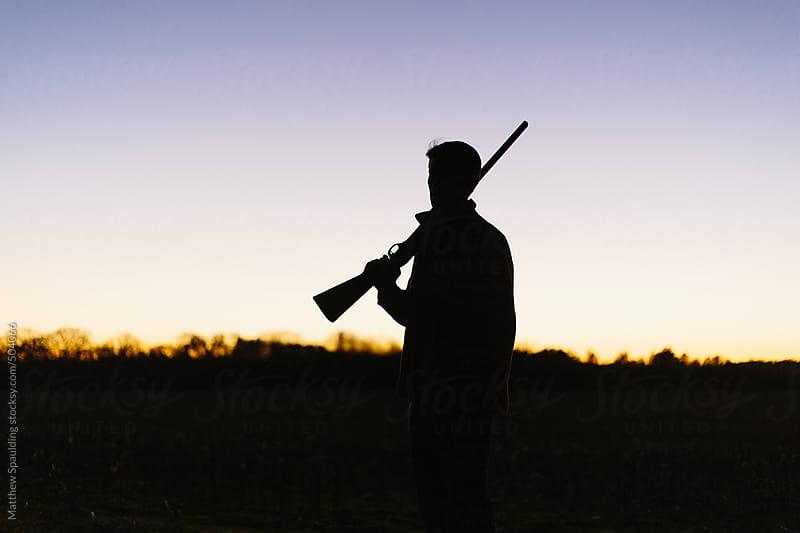 Silhouette of hunter holding gun on shoulder during hunt by Matthew Spaulding for Stocksy United