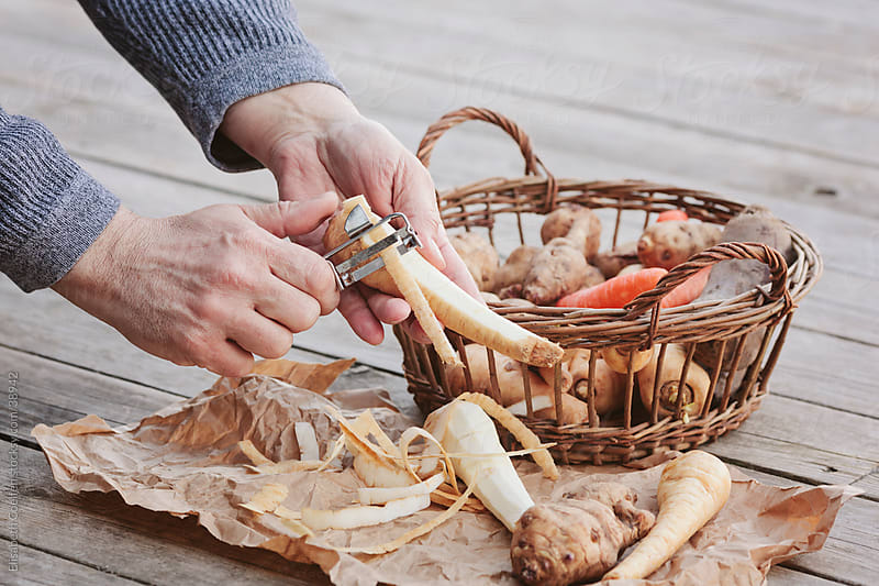 Male hands peeling some parsnips next to a basket filled with root vegetables by Elisabeth Coelfen for Stocksy United