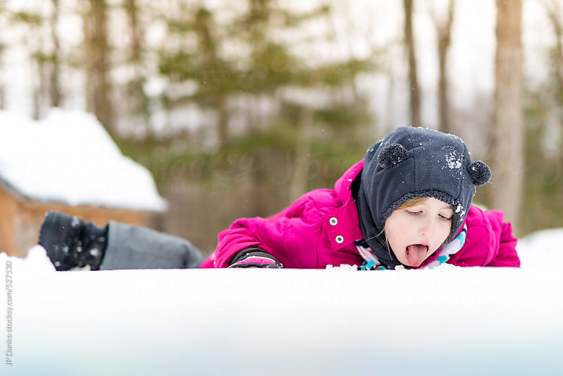 Little Girl Eating Snow in Winter Outdoors by JP Danko for Stocksy United