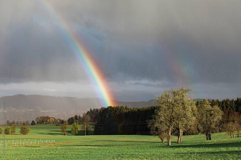Colorful rainbow arcing through stormy air by Amir Kaljikovic for Stocksy United