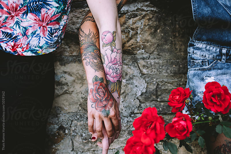 tattooed women holding her hands by Thais Ramos Varela for Stocksy United