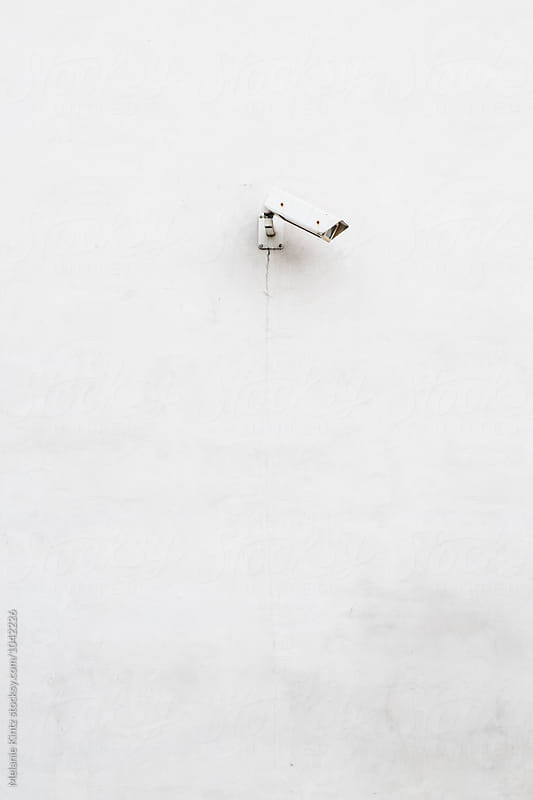 White surveillance camera on white wall, minimalist composition by Melanie Kintz for Stocksy United